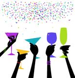 Stylish Women`s Hands Raising Glasses in a Toast. Hands holding cocktails raised in a celebratory toast with confetti Royalty Free Stock Images