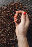 Hands holding coffee beans in shape of heart. Female hands holding coffee beans in shape of heart Royalty Free Stock Photography