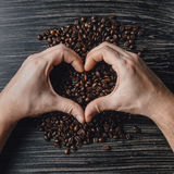 Hands holding coffee beans in shape of heart. Male hands holding coffee beans in shape of heart Stock Image