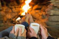 Hands holding coffee cups in front of lit fireplace Stock Images
