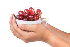 Hands holding coffee mug with a bunch of crimson red grapes Stock Photos