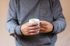 Holding a cup of coffee stock images
