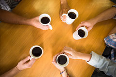 Hands holding coffee mugs on table Royalty Free Stock Images