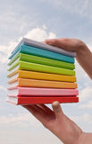 Hands holding color hard cover books Stock Photography