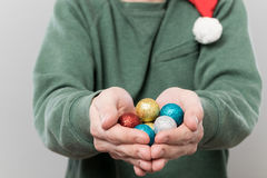 Hands holding colored balls. Hands holding multicolored decoration balls for christmas tree Royalty Free Stock Images