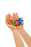 Hands holding colorful clay people Royalty Free Stock Image