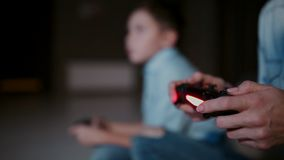 Hands holding a controller to a game console, and in the background the boy looks at the faucet and playing video games stock video footage
