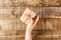 Hands holding craft paper gift box royalty free stock photo