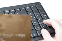 HANDS HOLDING CREDIT CARD ON KEYBOARD Stock Photo