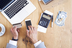 Hands holding credit card and paying bills on table Royalty Free Stock Photos