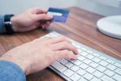 Hands holding credit card and a typing on keyboard making online purchase. Hands holding credit card and a typing on wireless keyboard making online purchase Stock Images