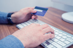 Hands holding credit card and a typing on keyboard making online purchase. Hands holding credit card and a typing on wireless keyboard making online purchase Stock Image