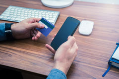 Hands holding credit card and a typing on the phone making online purchase. Copyspace on phone screen Royalty Free Stock Photos