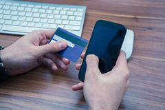 Hands holding credit card and a typing on the phone making online purchase. Copyspace on phone screen Royalty Free Stock Photography