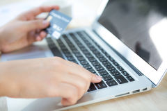 Hands holding a credit card and using laptop computer Stock Photos