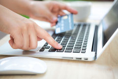 Hands holding a credit card and using laptop computer Stock Photography