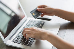 Hands holding a credit card and using laptop Stock Photography