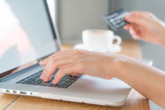 Hands holding a credit card and using laptop computer for online. Royalty Free Stock Photos
