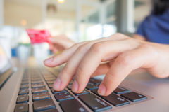 Hands holding a credit card and using laptop computer for online Royalty Free Stock Images