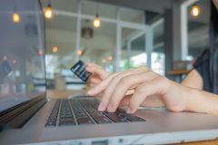 Hands holding a credit card and using laptop computer for online Royalty Free Stock Photography