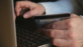 Close-up of hands with a credit card and using a laptop. Buying things. Online shopping stock video