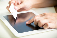 Hands holding a credit card and using tablet pc Stock Photo