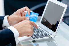 Hands holding credit cart by a laptop keyboard Royalty Free Stock Photos