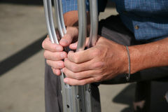 Hands holding crutches. Male hands holding his crutches after his accident Royalty Free Stock Images