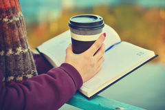 Hands holding cup and book Royalty Free Stock Image
