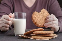 Hands holding cup of coffee and cookies on black background Stock Images