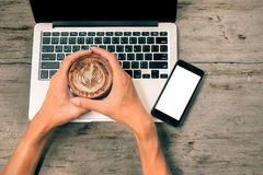 Hands holding cup of coffee and laptop and smart phone on wooden. Background with vintage filter effect, top view Royalty Free Stock Photos