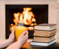 Hands holding cup of coffee near the fireplace Stock Image