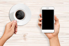 Hands holding a cup of coffee and White Smart phone Stock Photo