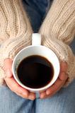 Hands holding cup of dark coffee Royalty Free Stock Images