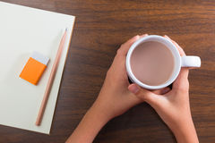 Hands holding cup of hot drink and stationary on table Royalty Free Stock Image