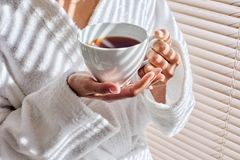 Hands holding cup of tea. Close up of female hands holding white cup of tea at spa salon, standing near window blinds, she`s wearing white robe royalty free stock images