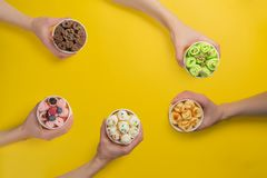 Hands holding cups with different rolled ice cream on bright yellow background. Top view stock photos
