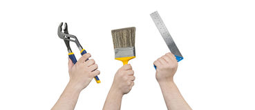 Hands Holding Curved Jaw Pliers, Paintbrush, and Square Ruler Stock Photos