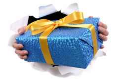 Hands holding delivering or giving small Christmas or birthday gift surprise through torn white paper background Royalty Free Stock Image