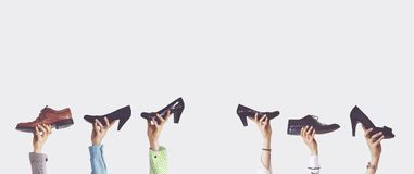 Hands holding different shoes on isolated background. Hands and hold stock photo