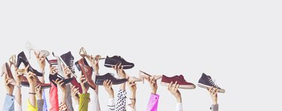 Hands holding different shoes on isolated background. Hands and hold stock image