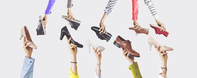 Hands holding different shoes on isolated background. Hands and hold stock photography