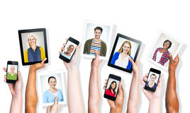 Hands Holding Digital Devices with People's Images Royalty Free Stock Image