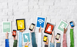 Hands Holding Digital Devices with Various Symbols Royalty Free Stock Photo