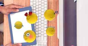 Hands holding digital tablet while emojis flying over computer desk. Digital composite of Hands holding digital tablet while emojis flying over computer desk Stock Photos