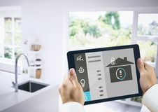 Hands holding digital tablet with home security icons Stock Image