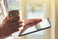 Hands holding digital tablet and morning coffee royalty free stock image