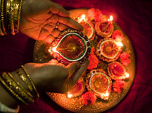 Hands holding Diwali lamps. Female hands holding traditional earthen Diwali lamps lit up in a line during Diwali festival in India Royalty Free Stock Photography