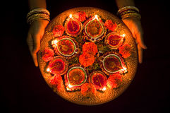 Hands holding Diwali lamps. Female hands holding traditional earthen Diwali lamps lit up in a line during Diwali festival in India