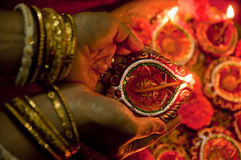 Hands holding Diwali lamps. Female hands holding traditional earthen Diwali lamps lit up in a line during Diwali festival in India Stock Images